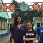 """Melody Liang, Zitong Li and David Tobiasz in front of signage that reads: """"Study hard, be a good person."""""""