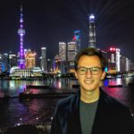 David Brenman, CESEAS alumnus, stands in front of Shanghai skyline at night