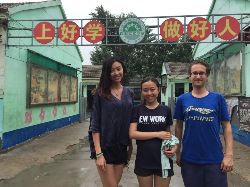 "Melody Liang, Zitong Li and David Tobiasz in front of signage that reads: ""Study hard, be a good person."""