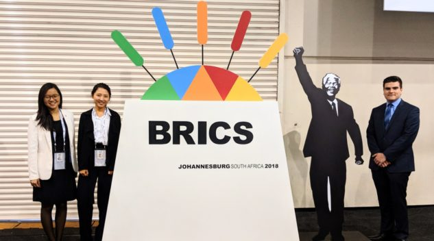 Alissa Wang, Angela Hou, and Ian Stansbury stand beside sign at 2018 BRICS Summit