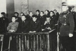 Black and white photograph of defendants at trial post World War II.