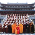 A group of buddhist monks stands in front of a temple.