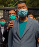 Hong Kong media tycoon Jimmy Lai, centre, who founded local newspaper Apple Daily, is arrested by police officers at his home in Hong Kong on April 18, 2020.