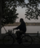 man rides bicycle by lake with mask on