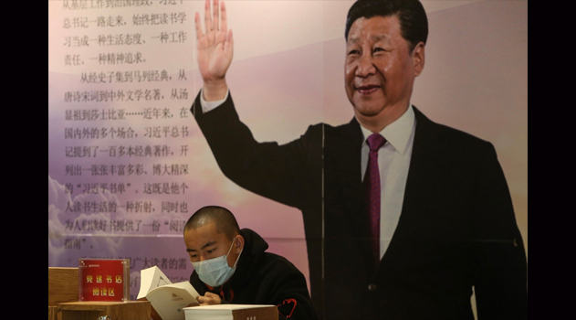 A man reads a book in front of a board with an image of China's President Xi Jinping at a book store in Shenyang, China, on April 23. STR/AFP VIA GETTY IMAGES