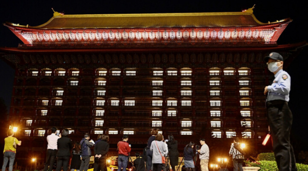 """People take photos as the rooms at the Grand Hotel are illuminated to form the word """"zero"""" after Taiwan reported no new coronavirus cases for two consecutive days, in Taipei on April 17. SAM YEH/AFP VIA GETTY IMAGES"""
