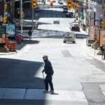 A pedestrian crosses an almost empty O'Connor Street in downtown Ottawa on May 14, 2020.