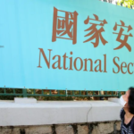 "woman wearing mask looks up at sign with Chinese characters and English message that says ""National Security Law"""