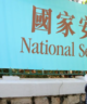 """woman wearing mask looks up at sign with Chinese characters and English message that says """"National Security Law"""""""