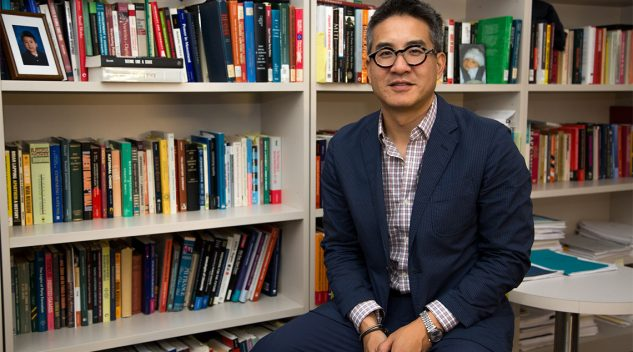 Joseph Wong sits in front of a bookshelf.