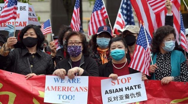 """Asian women wear masks and hold up signs """"we are Americans too!"""" and """"STOP Asian Hate"""" with American flags behind them."""