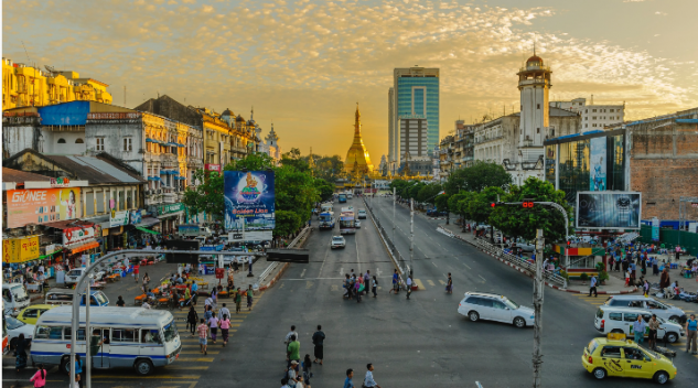 streetscape in Southeast Asia with golden pagoda in background