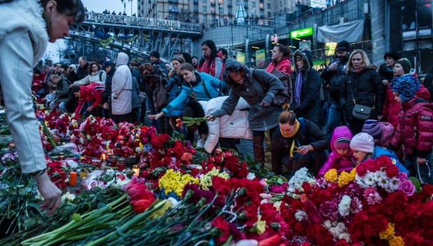"A photograph of people in Kiev laying flowers on the improvised memorial to the victims of shootings on the background of the slogan: ""the revolution must go on"""