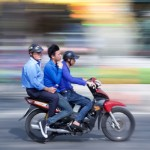Three people ride a motorcycle, with a blurred background, in Vietnam. Photo by Timothy Tse.