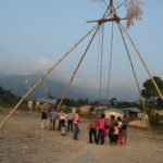 People by a swing and houses in front mountains