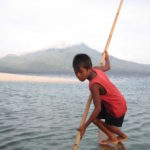 Boy holding a stick on a boat in the ocean and a cloudy mountain