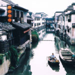 Chinese canal with two boats and houses