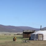 Woman sitting outside a yurt in daytime
