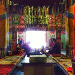 Monks sitting in a colourful room
