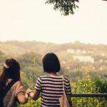Two girls looking at green hills