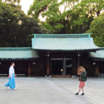Two people at a blue shrine and trees