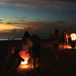 People lighting lanterns on the beach at night