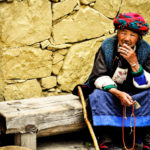 Old woman sitting with prayer beads