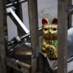 A golden cat statue sits atop a metal object.