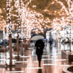 In this blurry photo, a person with an umbrella walks along a sidewalk surrounded by small trees covered in lights.