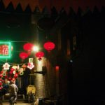 A man rides a bicycle through a dark alley lit by signs and red lanterns.