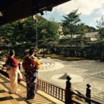 two women in kimonos look from a covered porch onto a zen sand garden.