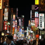 At night in Tokyo, the street is lit up with colourful signs and people fill the street.