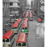 A street full of yellow buses with red roofs.