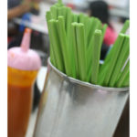 A container of green chopsticks and a bottle of hot sauce sit in the foreground, with blurry people eating at a table in the background.