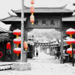 A gate flanked by red lanterns provides an entrance to a traditional village street.
