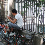 A man sits atop a bike leaning against a fence, reading on his phone.