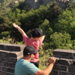 Man lifts boy on ledge of Great Wall of China to see the view.