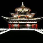 a Chinese temple is lit up from below against a black sky.