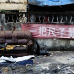 a deteriorating sofa sits outside amidst some garbage