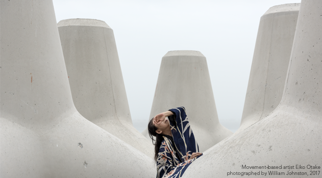 Movement-based artist Eiko Otake poses among concrete tetrapods.