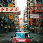 a taxi drives down a street filled with signs in Hong Kong.