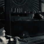 Elderly man smokes pipe in old teahouse in black and white photo