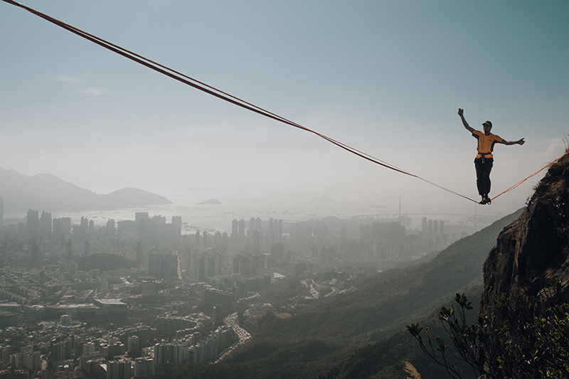 Melody (Chi Lok) Chan's photo, Lion Rock Spirit. The photo shows a figure balanced on a line suspended across Lion Rock mountain high above the misty skyline of Hong Kong.
