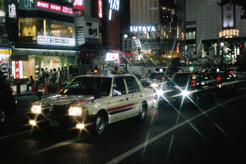 """Photo in Andy Takagi's """"Summertime in Tokyo"""" series. the image shows Taxi traveling through Shibuya crossing at night"""