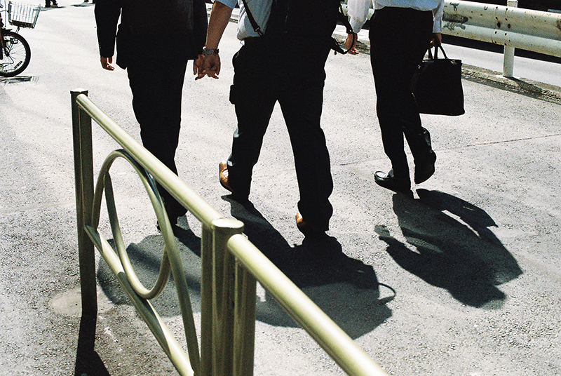 """Photo in Andy Takagi's """"Summertime in Tokyo"""" series; the image shows Salary-men walking in a hot summer day"""
