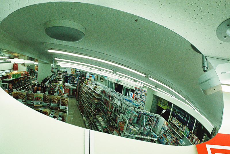 """Photo in Andy Takagi's """"Summertime in Tokyo"""" series; the image shows the inside of a convenience story from a curved mirror"""