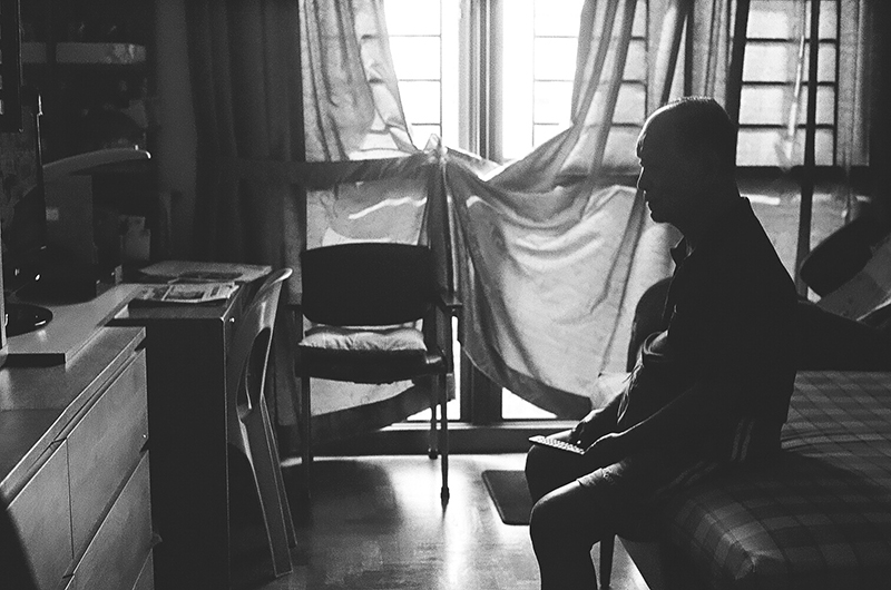 The first photo in Amanda Ann-Min Wong's series, Lest We Remember. The black and white photo shows an interior with a seated figure silhouetted in front of a curtained window.