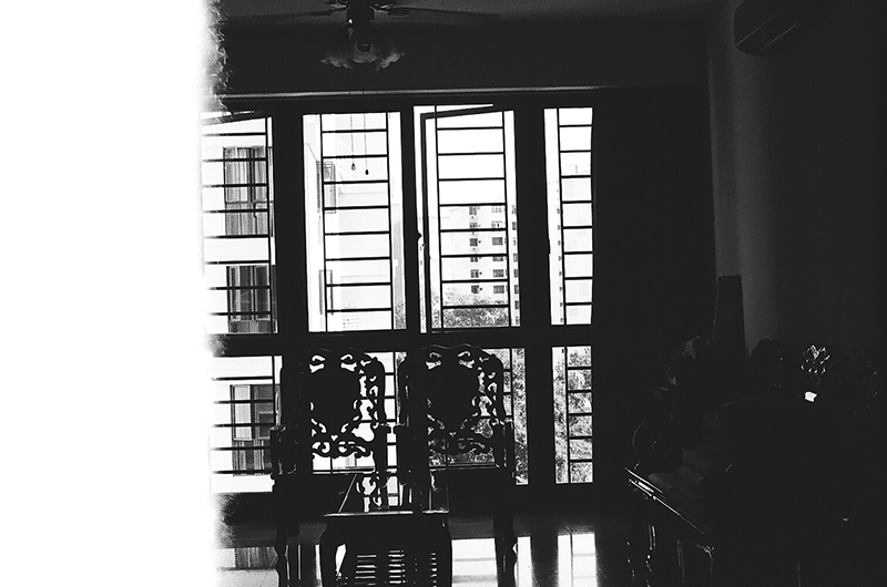The second photo in Amanda Ann-Min Wong's photo series, Lest We Remember. The partially exposed black and white photo shows two ornate chairs silhouetted in front of a window.