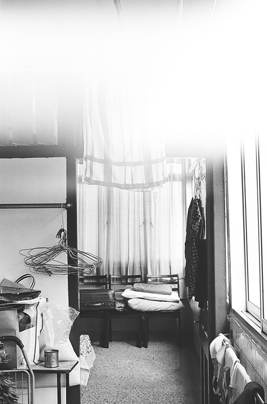 The third photo in Amanda Ann-Min Wong's series, Lest We Remember. A partially exposed black and white photo, the image shows the lower corner of a room with a small accumulation of objects such as clothes hangers and hanging clothing.