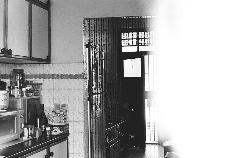 The fifth and final photo in Amanda Ann-Min Wong's series, Lest We Remember. The partially exposed black and white image shows a corner of a kitchen and an entryway hung with a beaded curtain.